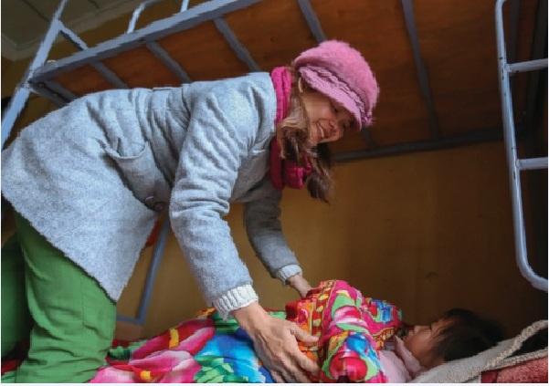 Giáo viên kiểm tra chăn màn học sinh trước giờ đi ngủ.