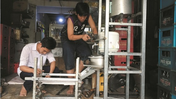 Duy và Khoa đang chế tác máy làm bánh xoài.