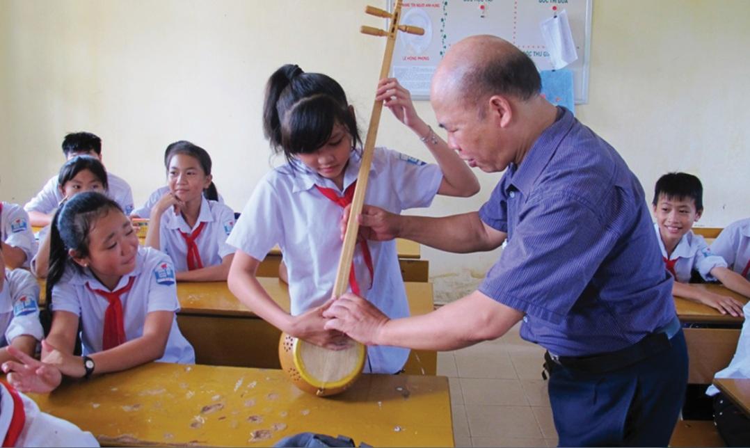 NNƯT Ma Văn Đức đang truyền dạy hát then, đàn tính cho học sinh.