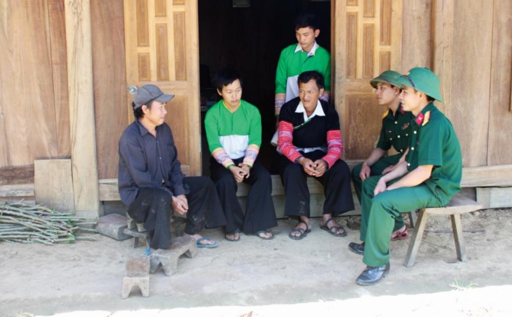 Bí thư Chi bộ Giàng A Chống (ngồi thứ 3 từ trái qua) cùng các chiến sĩ Bộ đội Biên phòng đến vận động bà con không nghe bọn xấu truyền đạo trái pháp luật.
