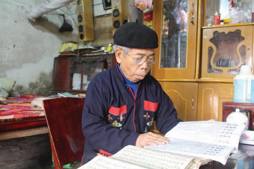 Ông Phùng Thế Vị bên cuốn sách cổ chép lại lời những bài hát giao duyên.