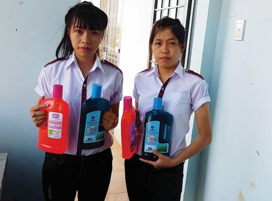 Hai em Mai và Hà với sản phẩm nước rửa chén, lau sàn nhà tinh dầu sả chanh.