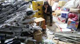 Chủ kho hàng Nguyễn Thị Nhiễu cùng tang vật là hơn 500 khẩu súng bắn điện, đạn, thanh kiếm, bình xịt hơi cay do Trung Quốc sản xuất