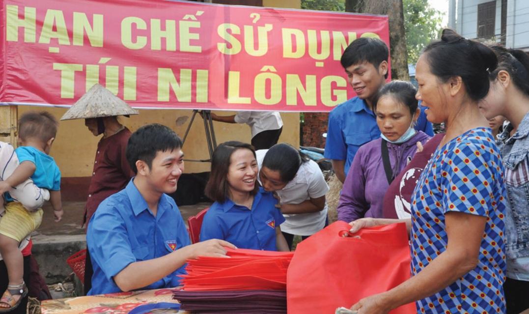 Hội Liên hiệp Phụ nữ và Đoàn xã Liên Chung cấp phát túi thân thiện với môi trường cho người dân.