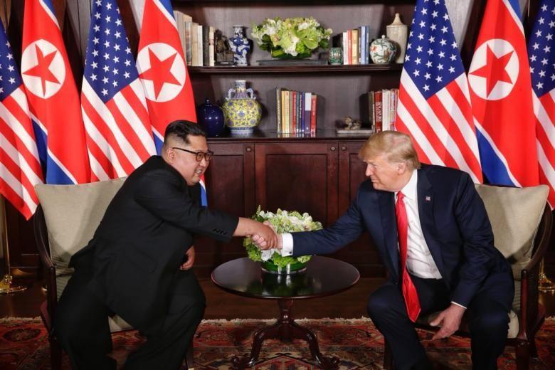 Tổng thống Mỹ Donald Trump và nhà lãnh đạo Triều Tiên Kim Jong-un trong thư viện của khách sạn Capella Singapore. Ảnh: The Straits Times