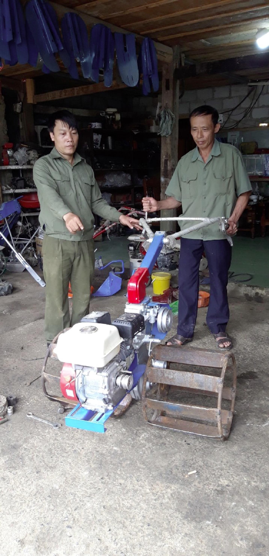 Anh Nguyễn Văn Tuấn (bên trái) hướng dẫn người dân cách sử dụng máy.