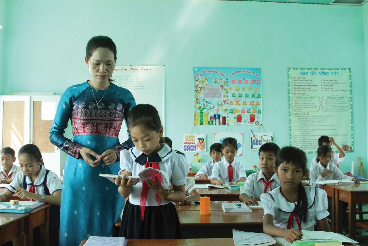 Giáo viên dân tộc Chăm trong trang phục truyền thống đến trường dạy chữ cho học sinh.
