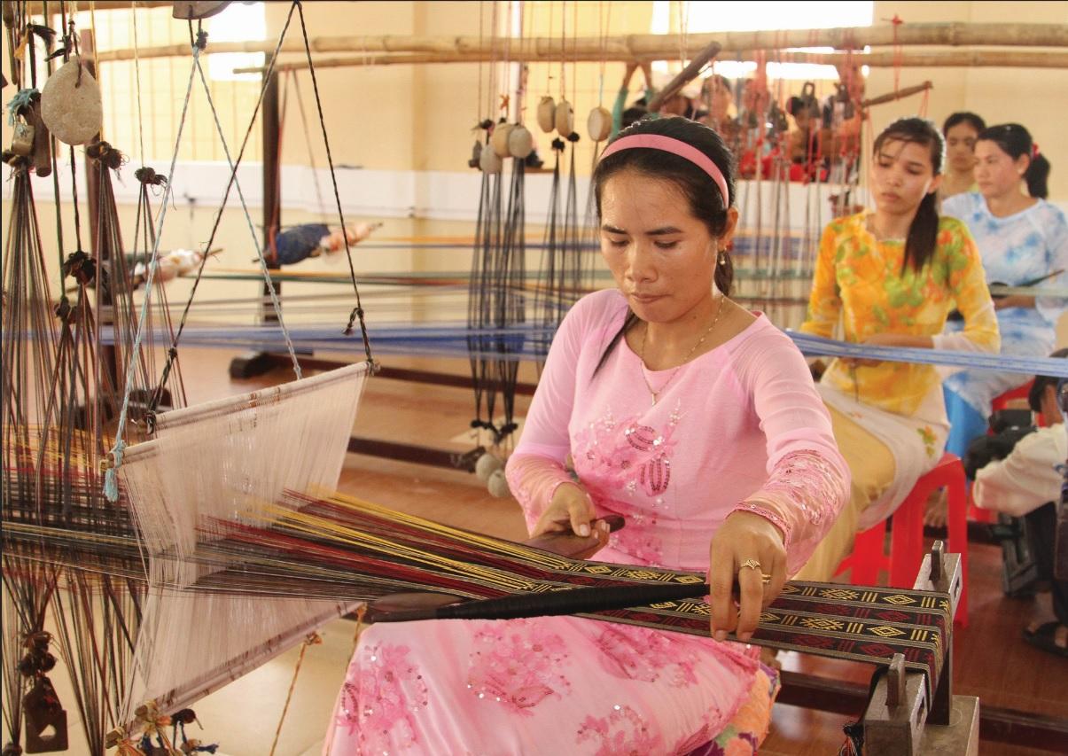 Phụ nữ Chăm trong trang phục truyền thống đang dệt thổ cẩm.