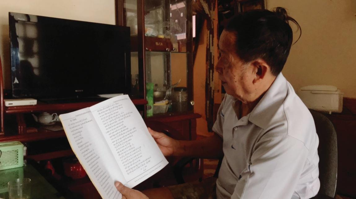 Ông Lò Văn Thâng thông tin về tài liệu dạy chữ dân tộc Thái do ông biên soạn.
