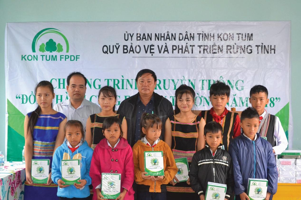 Lãnh đạo Quỹ và nhà trường cùng trao vở cho các em học sinh.