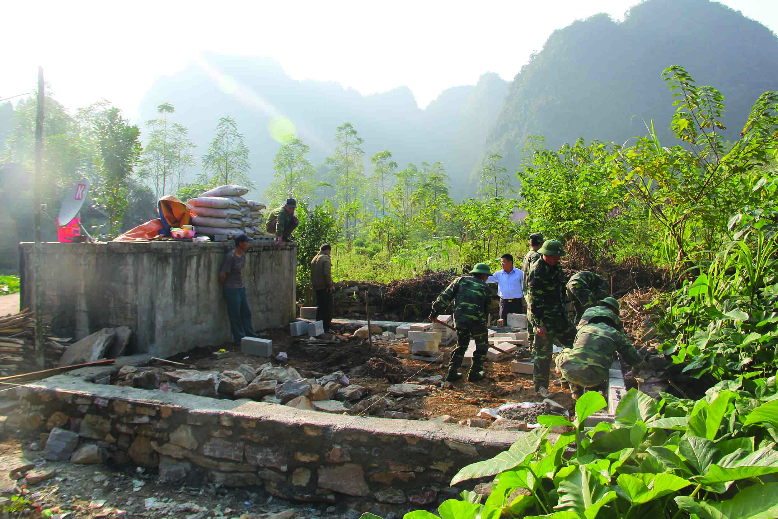Bộ đội Biên phòng giúp dân xây dựng nhà cửa, chuồng trại. (Ảnh: Hiếu Anh)