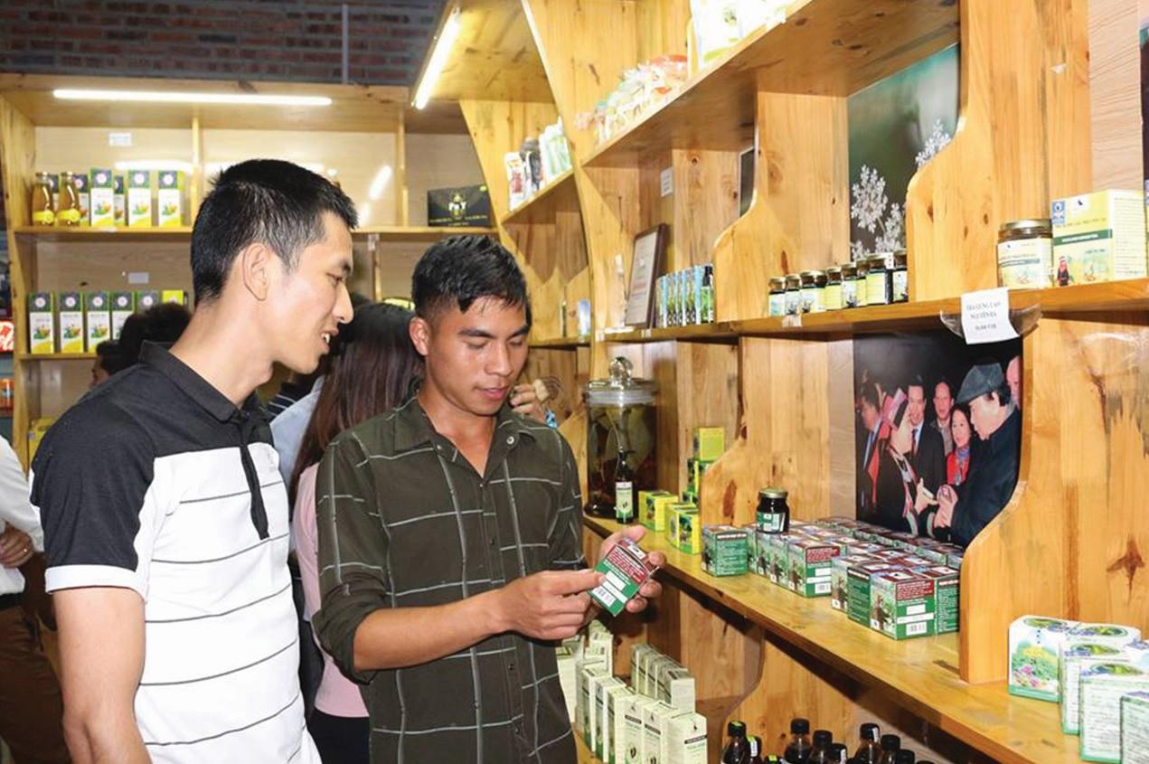 Lý Tà Giàng đang giới thiệu sản phẩm mạnh gân hoạt cốt cho khách du lịch tại gian hàng dược liệu của mình.