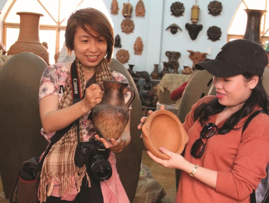 Du khách thích thú với sản phẩm gốm Chăm Bàu Trúc.