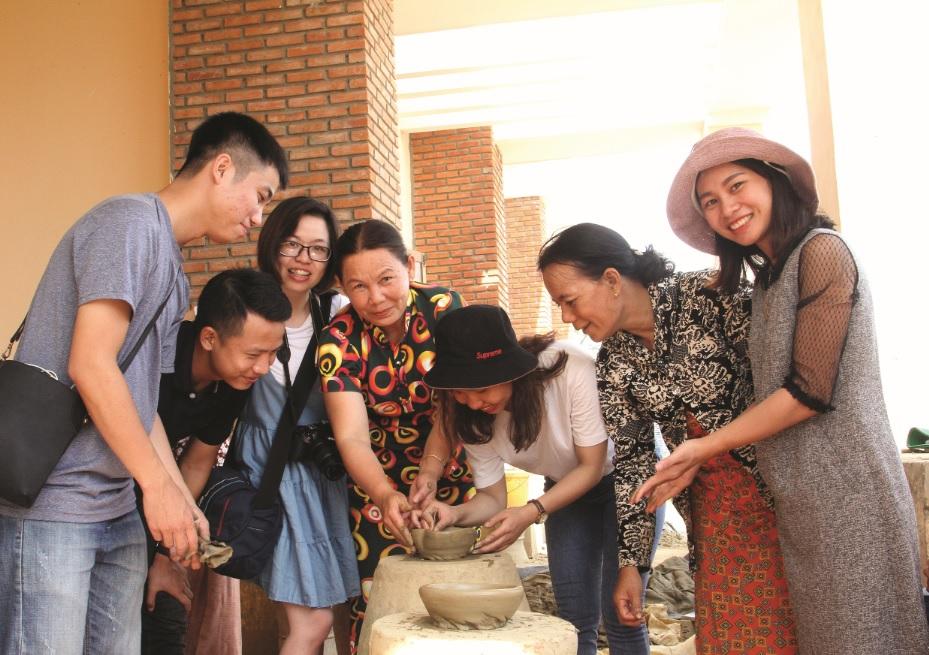 Nghệ nhân Trượng Thị Gạch hướng dẫn du khách trải nghiệm chế tác gốm.