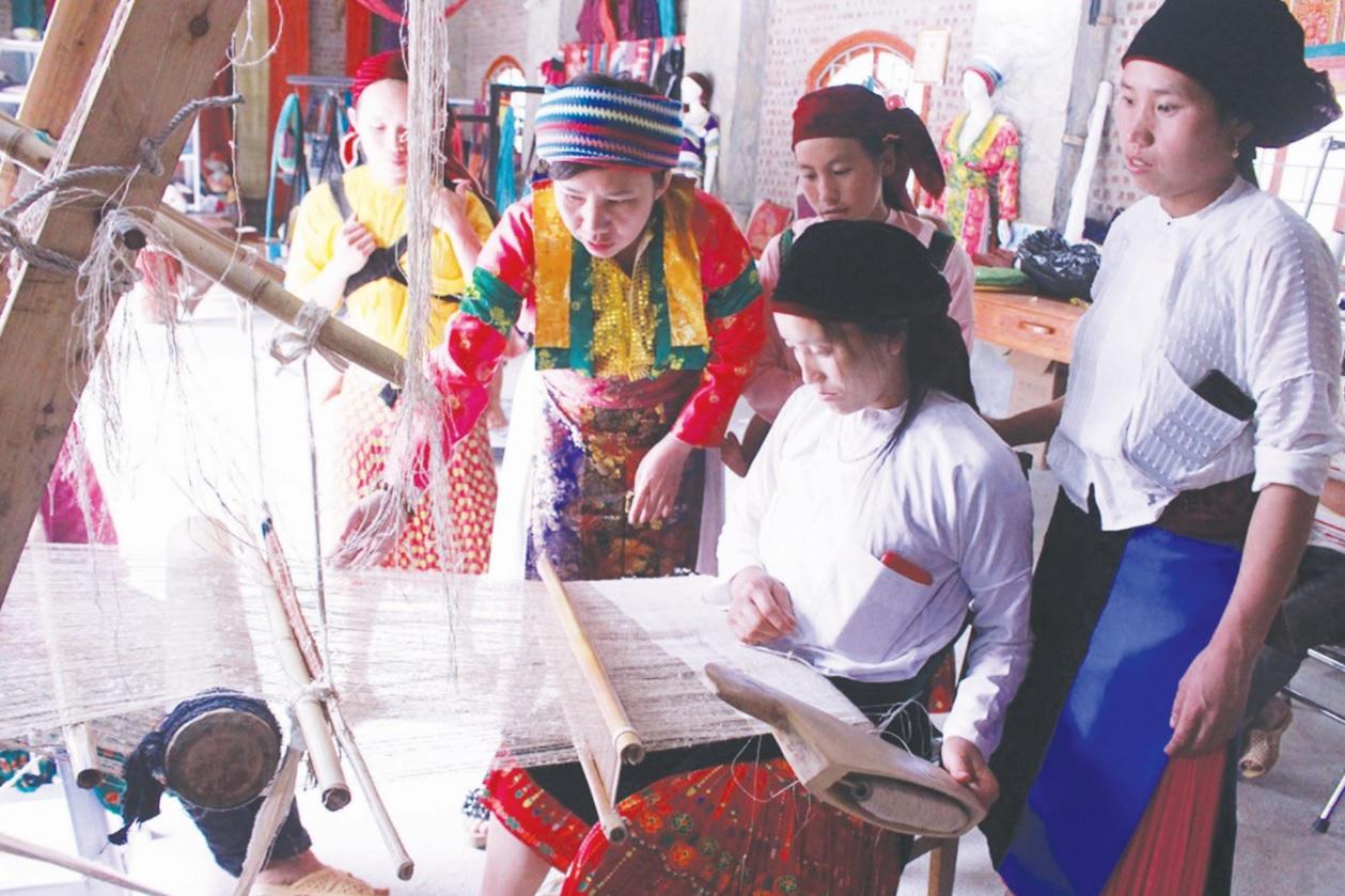 Chị Vàng Thị Cầu (đứng thứ 2 từ trái sang) Giám đốc HTX Lanh Trắng đang hướng dẫn chị em người Mông dệt lanh.