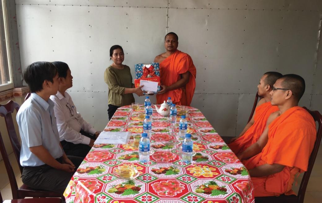 Bà Huỳnh Thị Sô Ma Ly, Vụ trưởng Vụ Địa phương 3 (UBDT) tặng quà cho Đại đức Thạch Điệp, Phó chủ trì chùa Pôthi Sômrom, thành viên Quản trị Học viện Phật Giáo Nam tông Khmer.