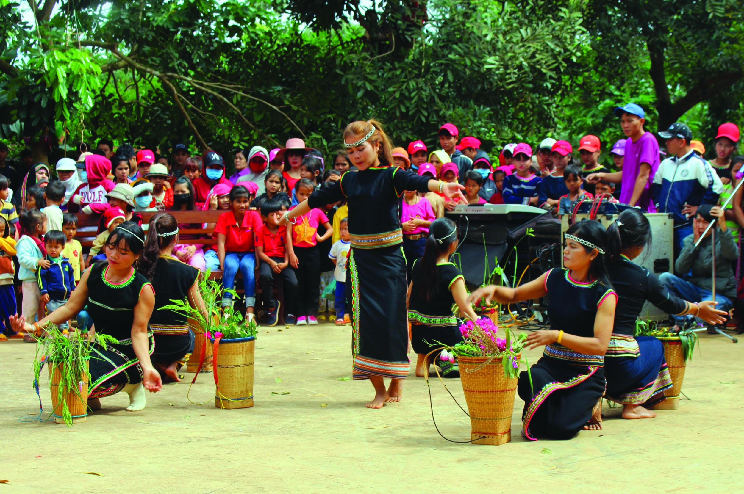 Các cô gái Xơ-đăng trong trang phục truyền thống múa bài mừng lúa mới.