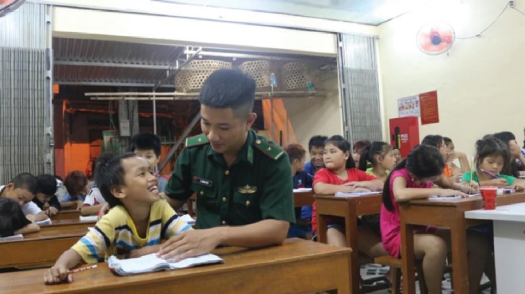 Thiếu úy Lê Hồng Việt giảng bài cho em nhỏ lớp tình thương.