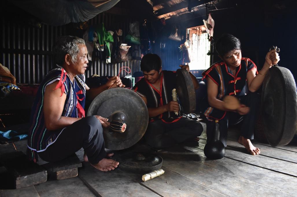 Rơ Châm Van (ngồi giữa) thử âm thanh cồng chiêng cùng các nghệ nhân trong buôn.