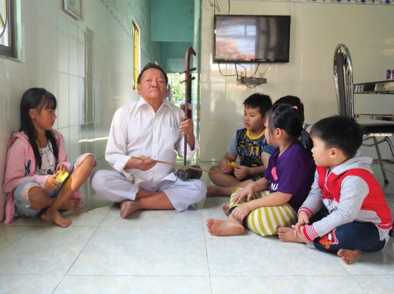 Nghệ nhân Trần Biểu dạy hát sắc bùa cho trẻ em trong xóm.