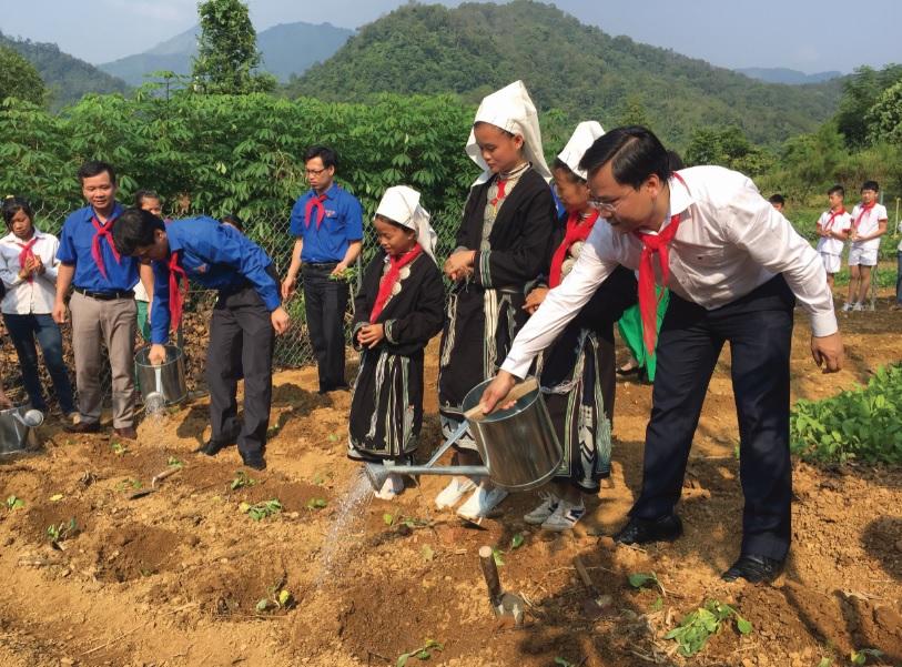 """Ông Nguyễn Anh Tuấn (ngoài cùng bên phải) chăm sóc """"Vườn rau cho em"""" cùng các cháu thiếu niên Trường Phổ thông dân tộc Bán trú Cốc Đán, Ngân Sơn, Bắc Kạn."""