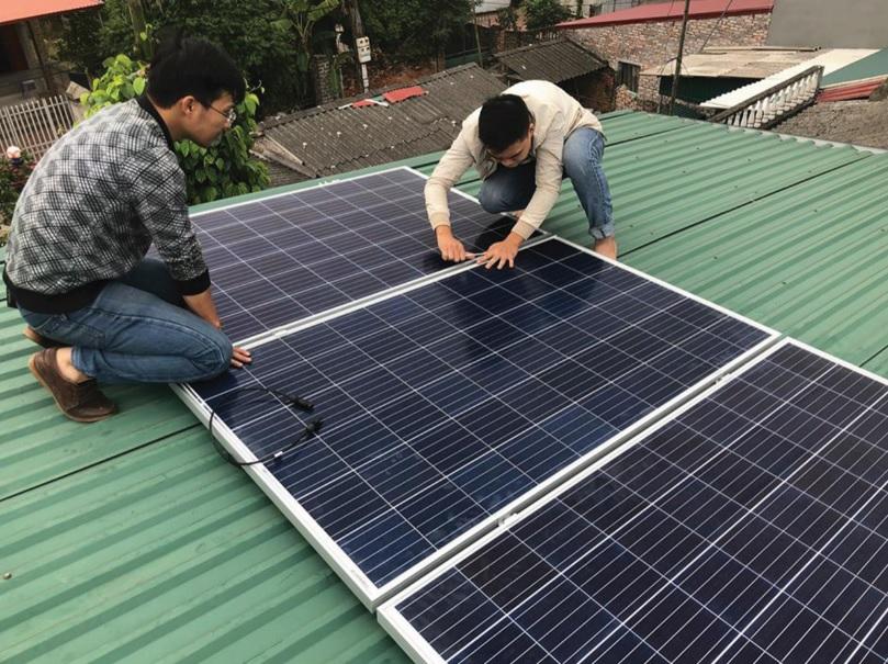 Công nhân đang lắp đặt hệ thống điện mặt trời trên nhà người dân.