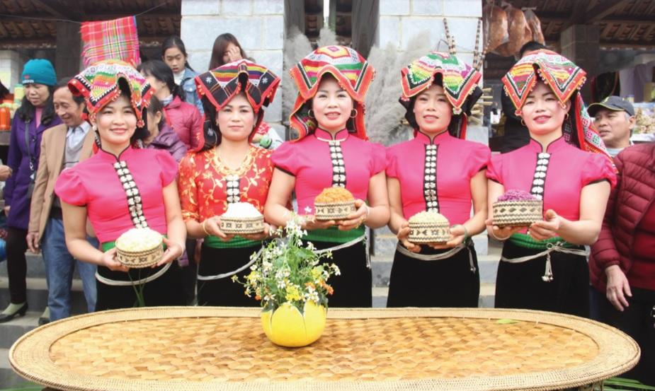 Những nét đặc trưng trong trang phục DTTS cần được bảo tồn. (Trong ảnh: Đồng bào dân tộc Thái, tỉnh Sơn La trong trang phục truyền thống giới thiệu ẩm thực của dân tộc mình tại Làng Văn hóa, Du lịch các dân tộc Việt Nam)