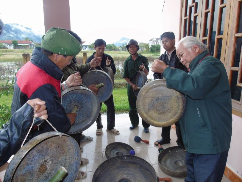 """Nghệ nhân Yang Danh (ngoài cùng bên phải), một trong những người """"giữ hồn"""" của buôn làng Ba Na dạy bà con cách đánh cồng chiêng."""