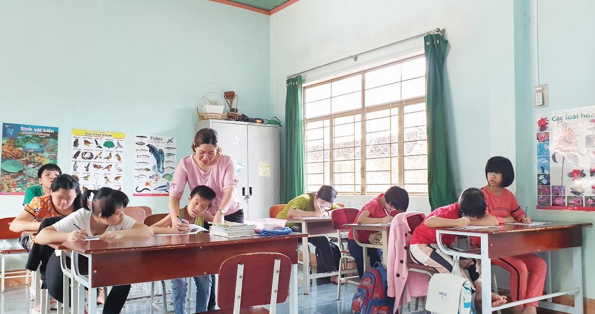 Cô giáo H'Khuin dạy học cho học sinh là nạn nhân của di chứng chất độc da cam
