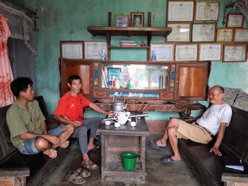 Ông Lê Xuân Trị (người áo đỏ bên trái) và ông Lò Văn Tuyên (bên phải) đều phấn khởi vì có con trai đang đi XKLĐ có thu nhập cao.