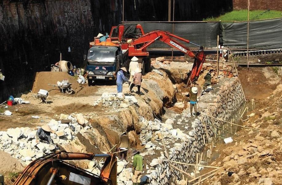 Xe múc đào bới bờ kè hộ thành hào Kinh thành Huế để tiến hành tu bổ, xây mới di tích này. (Ảnh tư liệu)