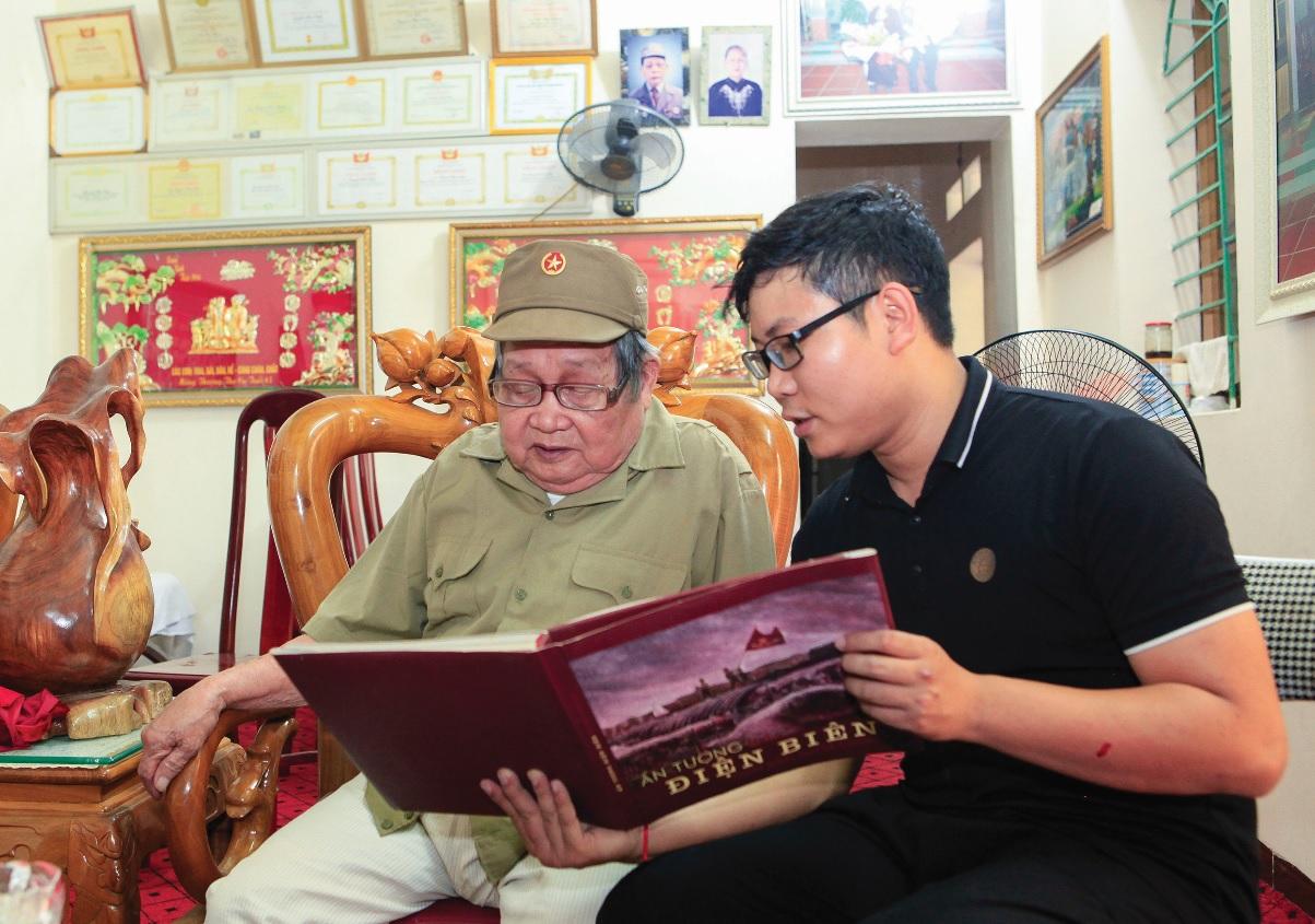 Cựu chiến binh Nguyễn Hữu Chấp (bên trái) ôn lại kỷ niệm về chiến dịch Điện Biên Phủ qua những trang sách.