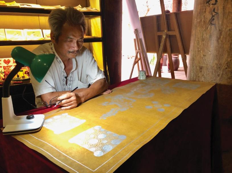 """Nghệ nhân Lại Phú Thạch đang phục dựng lại bản sắc phong để trưng bày trong triển lãm """"Dó Việt xưa và nay""""."""