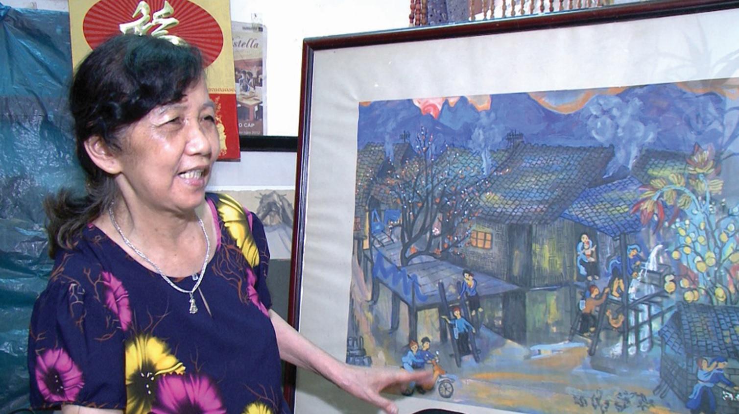 Họa sĩ Chu Thị Thánh bên tác phẩm của mình.