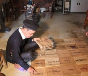 Nghệ nhân Ưu tú Triệu Văn Quẩy với những cuốn sách cổ bằng chữ Dao mà ông sưu tầm được trong suốt hơn 40 năm.