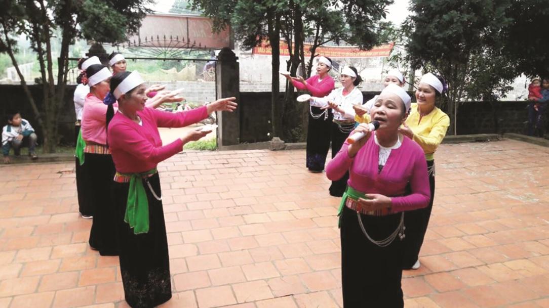 Bà Đinh Thị Hiền (người cầm micro) cùng CLB Hội Người cao tuổi xã Minh Quang tập luyện văn nghệ.