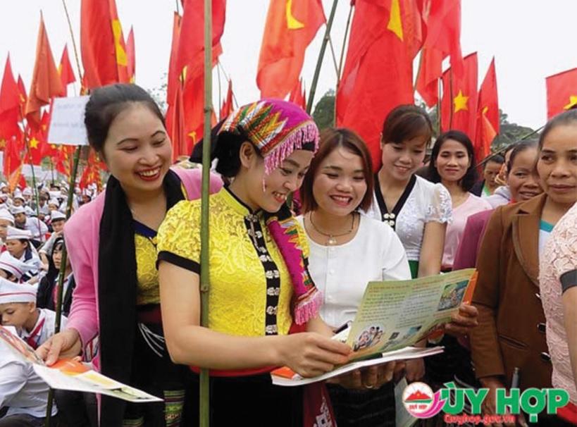 Chị em phụ nữ dân tộc Thái tiếp cận thông tin trong tờ rơi tuyên truyền về dân số.