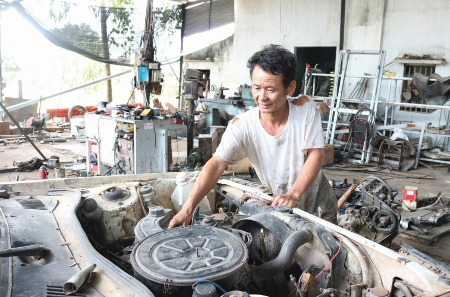 Ông Nguyễn Đình Long đang sửa chữa xe ô tô tại xưởng của mình.