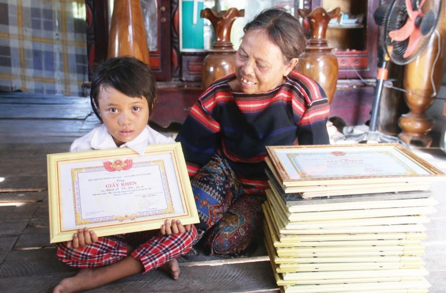 Bà Rmah H'Đoan khoe Giấy khen và thành tích học tập của con cháu.