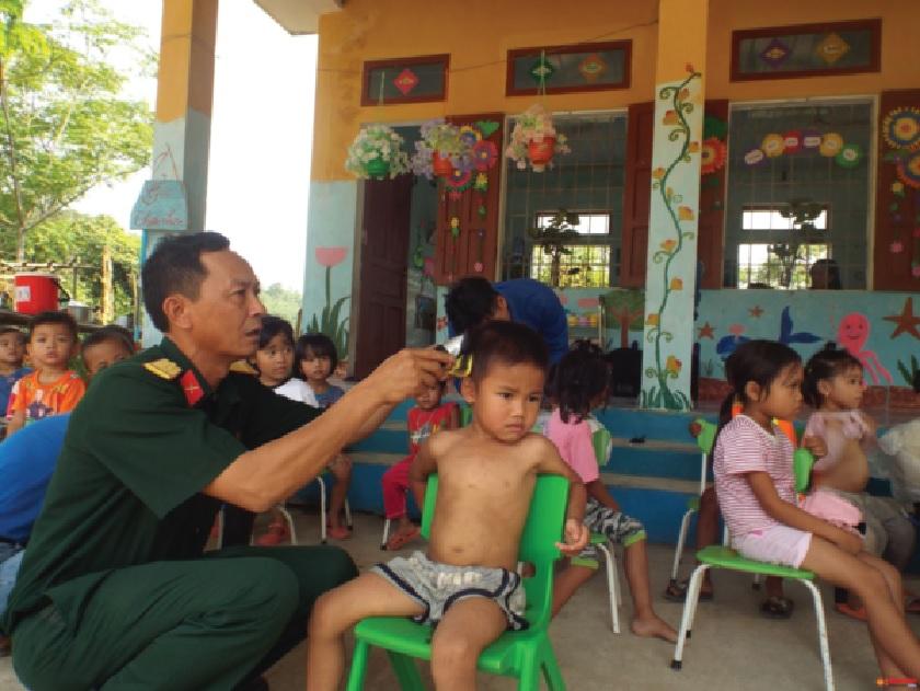 Cán bộ, chiến sĩ Ban CHQS Tuyên Hóa cắt tóc, vệ sinh cá nhân cho các em học sinh người Mã Liềng. Ảnh: TL