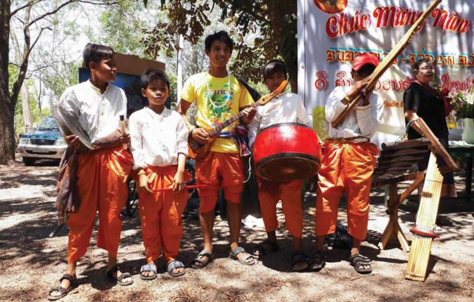 Anh Y Nô Ly Kbuôr (giữa) và học trò đi biểu diễn tại lễ hội.