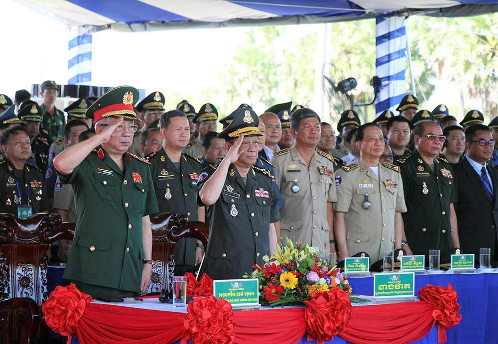 Các đại biểu Việt Nam và Campuchia thực hiện nghi lễ chào cờ.