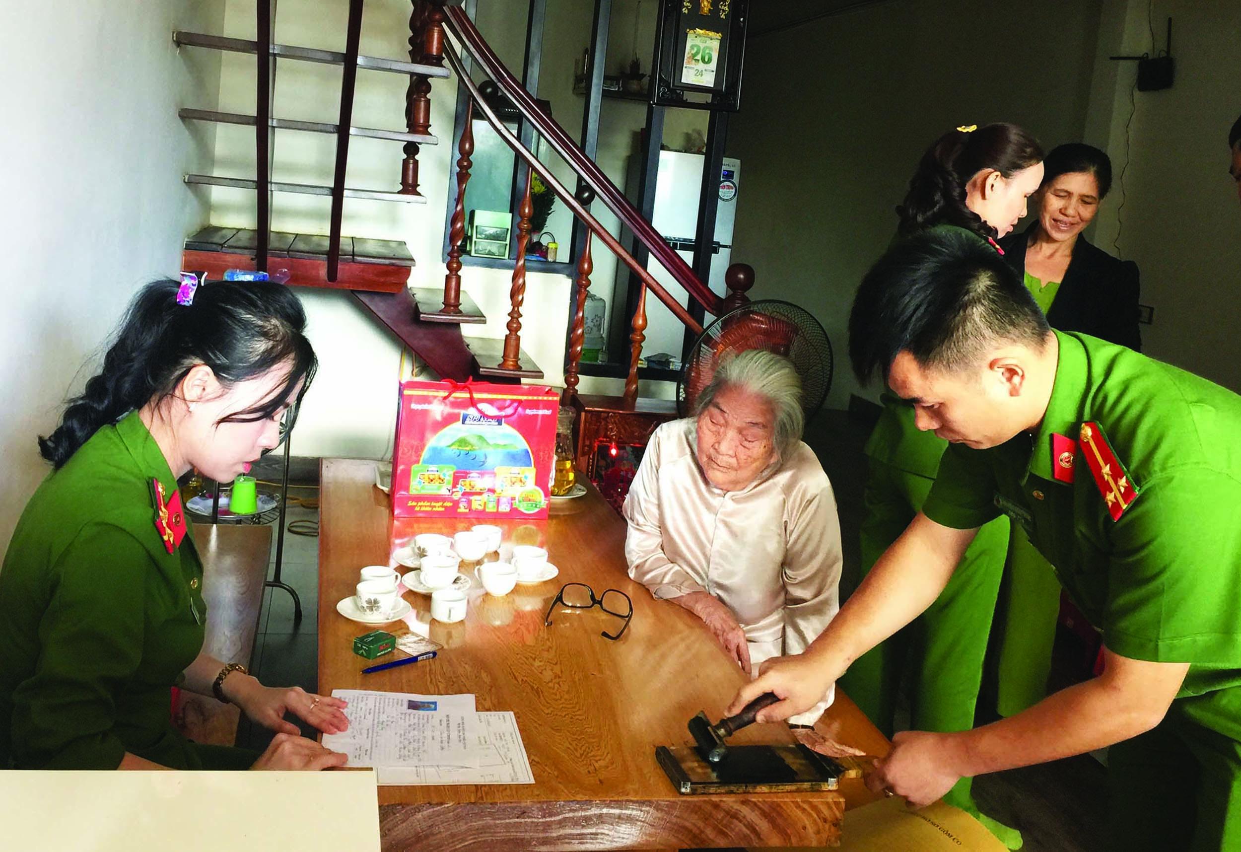 Các cán bộ, chiến sĩ công an làm thủ tục cấp giấy CMND cho Mẹ Việt Nam Anh hùng Hồ Thị Chúng.