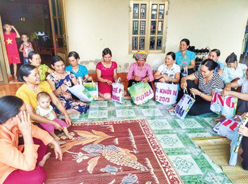 Chị em phụ nữ xã Mường Báng, huyện Tủa Chùa, tỉnh Điện Biên vui mừng với chiếc túi mới được tái chế từ pano, áp phích. Ảnh: Hoàng Châu