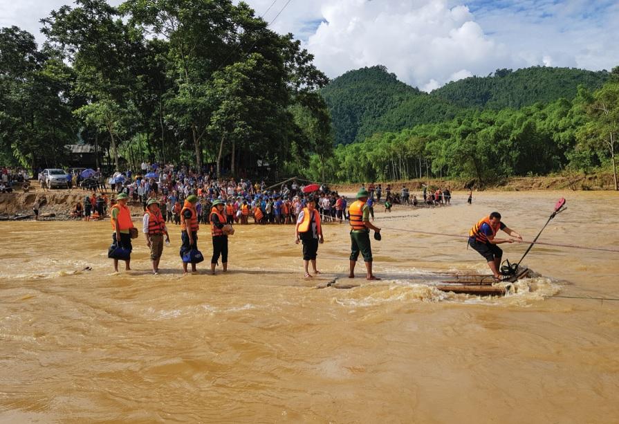 Vượt sông bằng bè mảng đến với bà con vùng lũ dữ tại bản Sa Ná, huyện Quan Sơn, Thanh Hóa.
