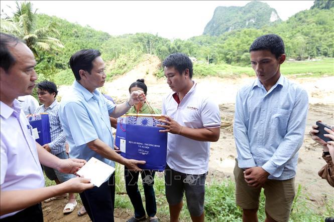 Bộ trưởng Bộ Lao động - Thương binh và Xã hội Đào Ngọc Dung tặng quà các gia đình bị thiệt hại nặng nề do ảnh hưởng mưa lũ tại bản Sa Ná, xã Neo Mèo, huyện Quan Sơn. (Ảnh: Anh Tuấn/TTXVN)