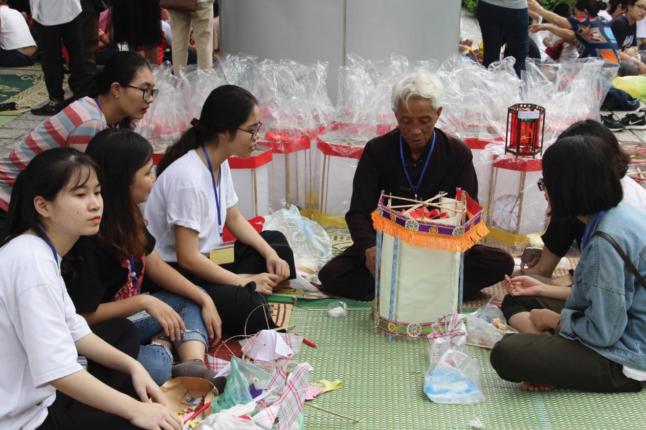 Ông Nguyễn Văn Quyền hướng dẫn các em học sinh làm đèn kéo quân tại Bảo tàng Dân tộc học Việt Nam.