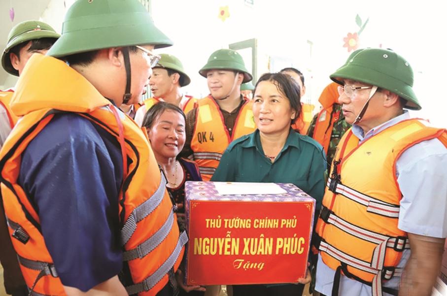 Bộ đội Biên phòng cửa khẩu quốc tế Lao Bảo giúp dân vệ sinh nhà cửa sau khi lũ rút.